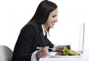 Profile of a businesswoman eating and using a laptop
